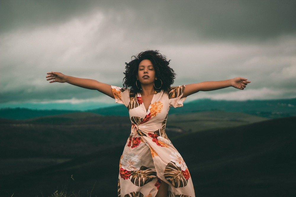 Woman-with-arms-outstretched-in-the-mountains