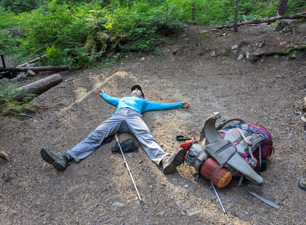 Woman-laying-on-trail-tired-from-backpacking-course