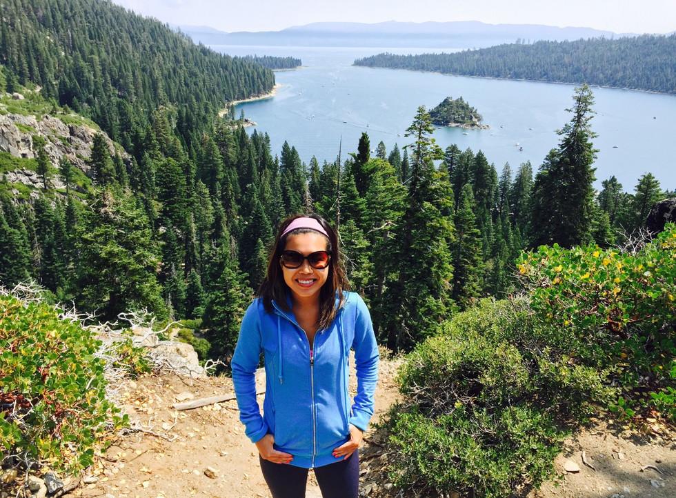 Woman-smiling-at-hike-viewpoint-of-lake