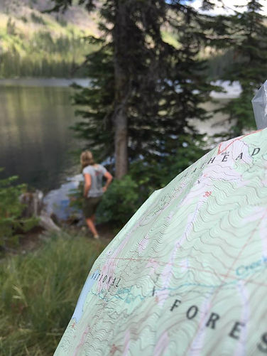 Close-up-of-topo-map-with-woman-and-lake-in-background