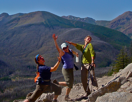 Three-hikers-striking-silly-poses-on-womens-adventure