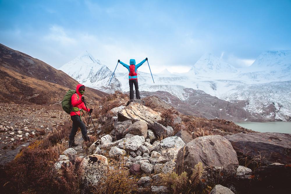 woman-backpacker-reaching-towards-sky-on-hike