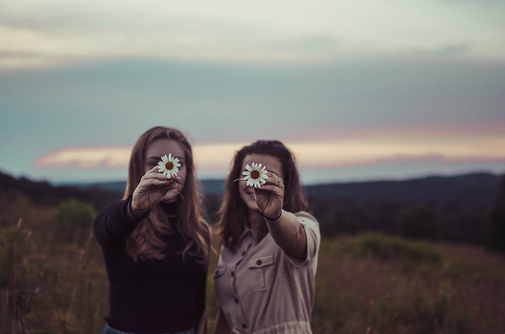 two-woman-holding-flowers-in-front-of-their-faces-outside