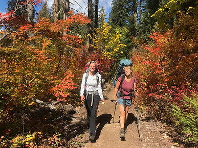 Two-backpackers-smiling-with-fall-colors-on-trail