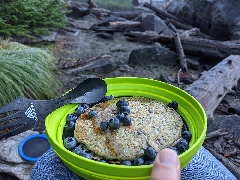 Hand-holding-blueberry-pancakes-in-backcountry