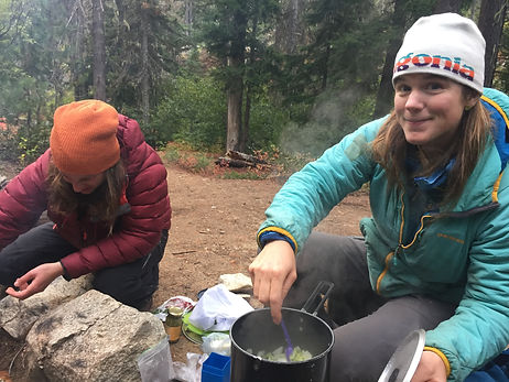 Woman-smiling-while-backcountry-cooking