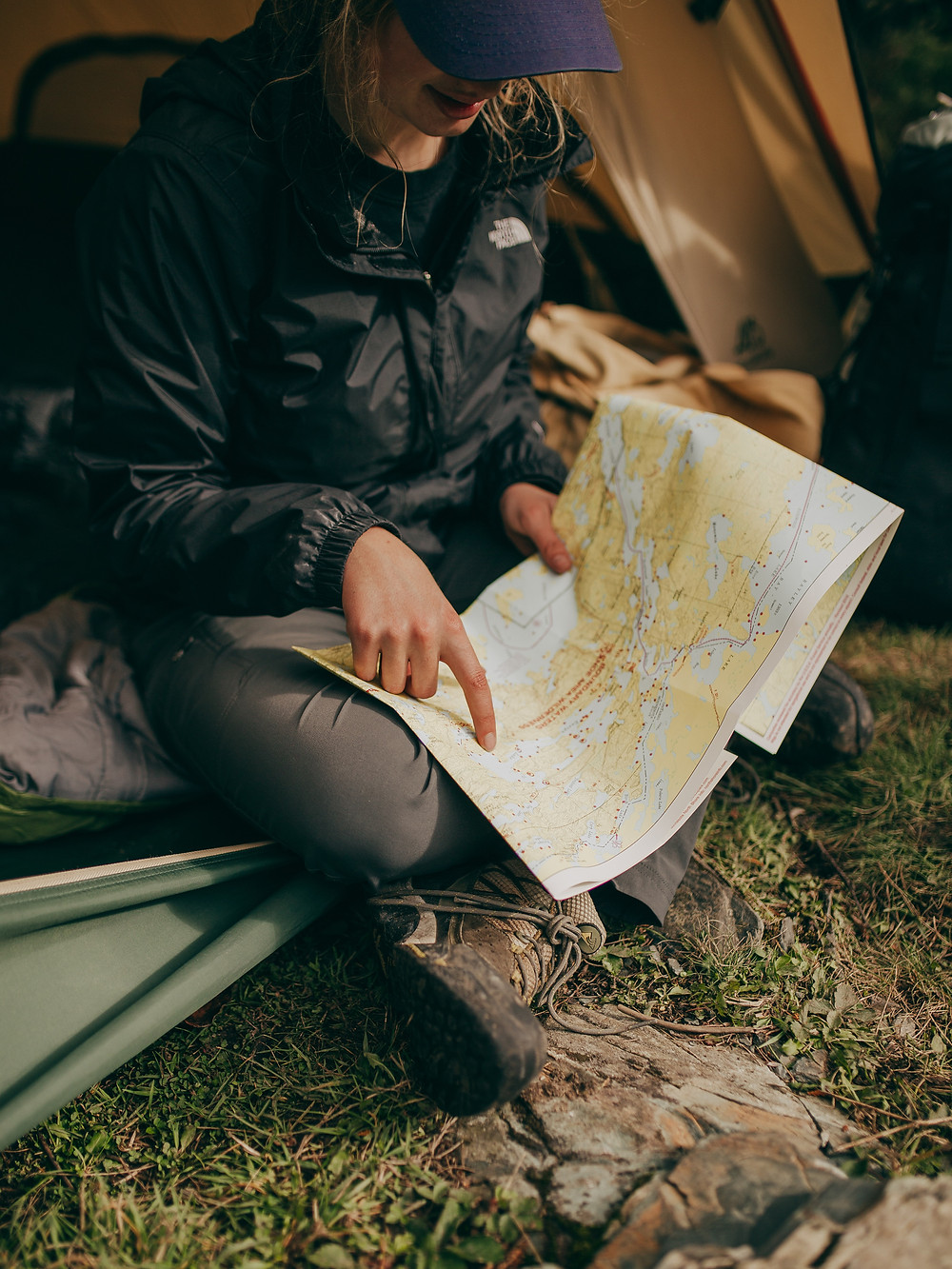 woman-sitting-in-tent-and-pointing-at-map-in-hand