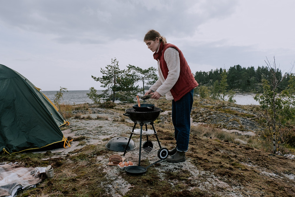 woman-backcountry-cooking-on-grill-near-water