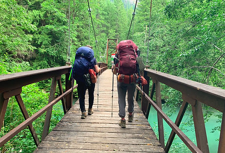 two-backpackers-walking-on-bridge-over-river