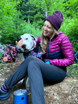 Woman sitting next to dog while camping