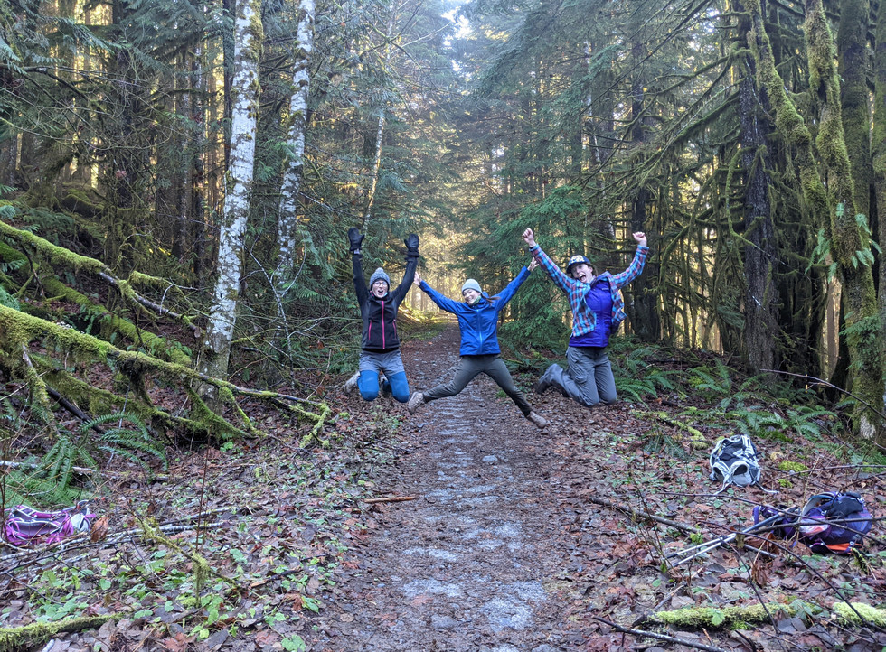 Three-woman-jumping-over-a-trail-during-backpacking-course