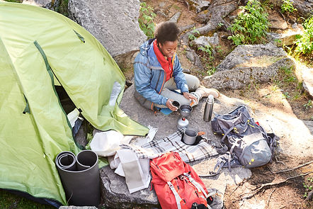 Woman-setting-up-backcountry-stove-by-her-tent