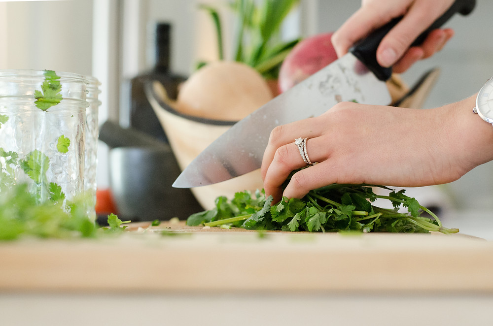 Woman chopping herbs in kitchen