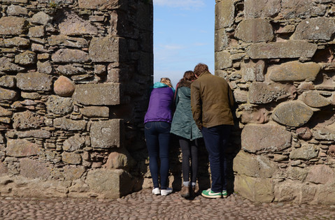 A family looking over a parapet in a castle in Scotland