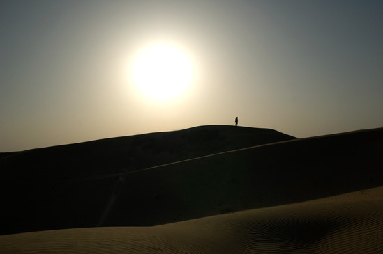 A tourist photographing the dunes in the That desert