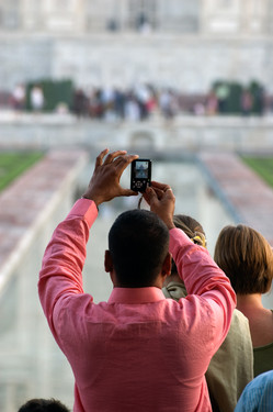 A man photographs the Taj Mahal. There is a certain spot where people wait to capture the quintessential photograph of the Taj