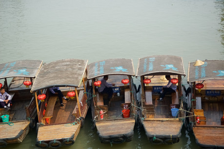 Boat guides wait to take tourists round the water town of Qibao