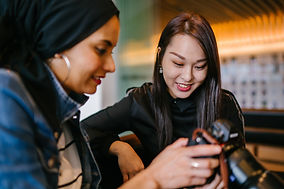 woman-looking-to-woman-holding-dslr-came