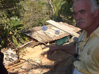 Dr. Hoefflin pointing out that 6 children live in this shack.