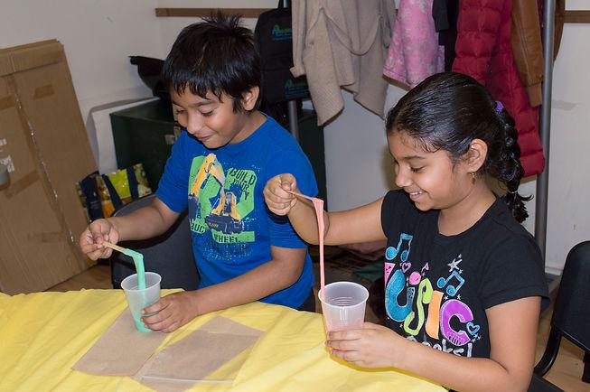 Two children creating their own colourful glue.