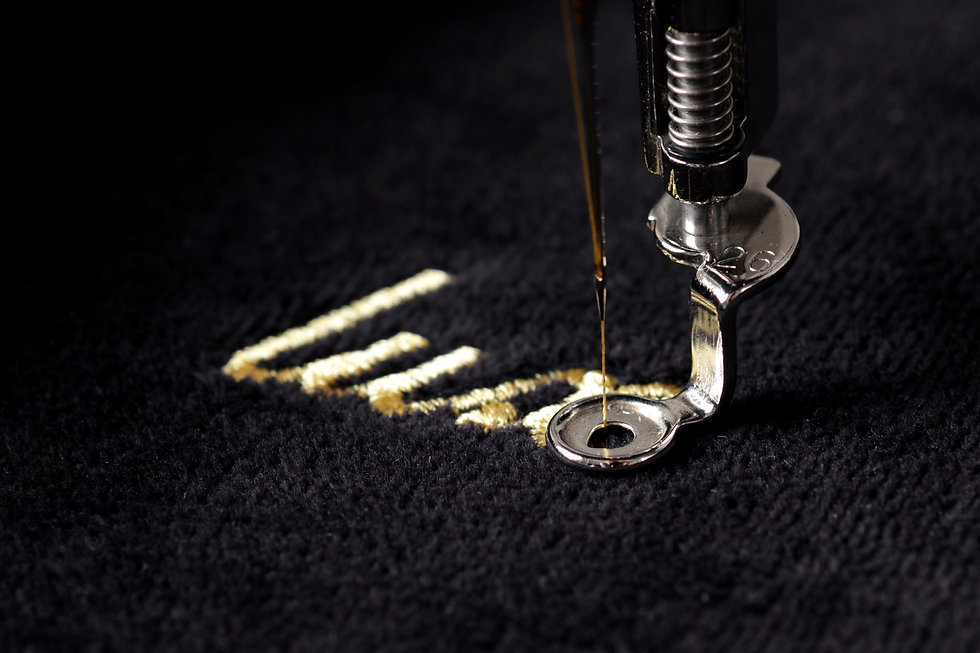 embroidery of gold lettering _luxury_ on black velvety fabric with embroidery machine - detail of be