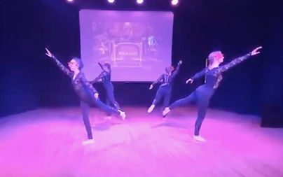 An image of four dancers, dressed in black all in one suits, dancing a ballet dance in a show.