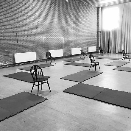 A sports hall set up for a dance class. There are mats and chairs out ready.