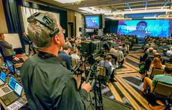 Cameraman filming meeting.