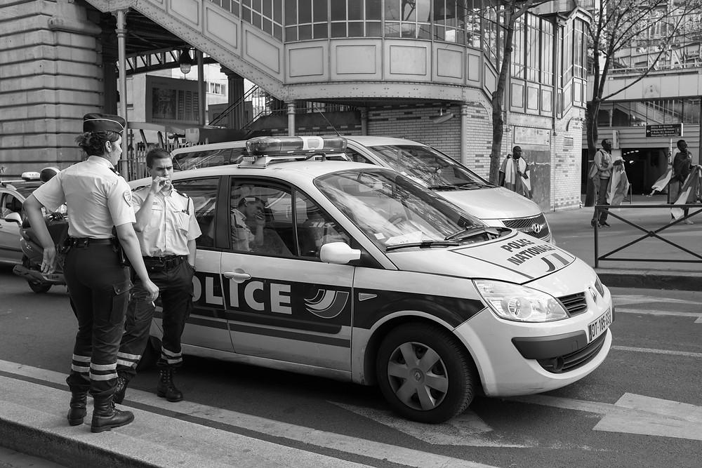 パリ15区グルネル通りの路上にパトカーを停めて一服する警察官(2016年6月)