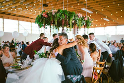 Suspended Head Table Floral installation dripping with greenery and blooms.