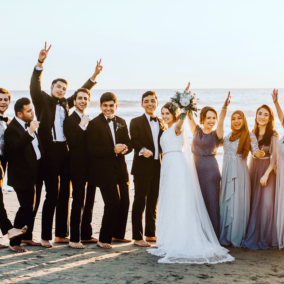 Bride & Groom celebrate on the beach in Malibu after their wedding ceremony overlooking the ocean. They are surronded by their wedding party, groomsmen and bridesmaids as they cheer on the newlyweds.