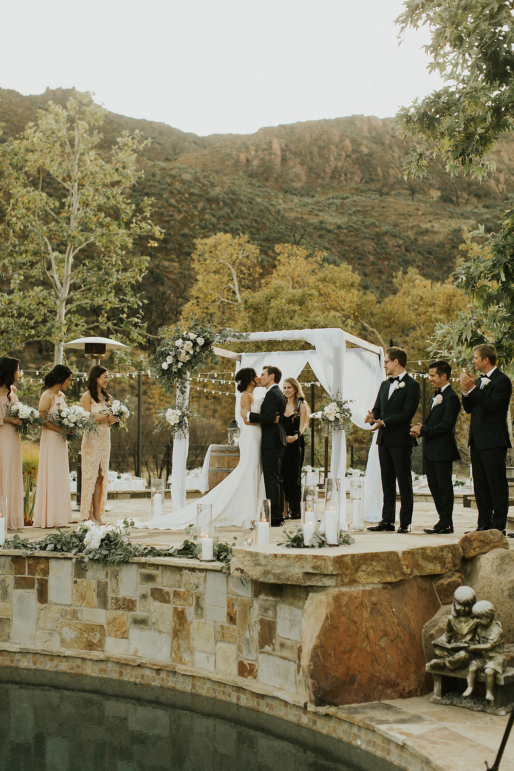 Couple kiss after saying I Do in a Backyard wedding designed around the pool