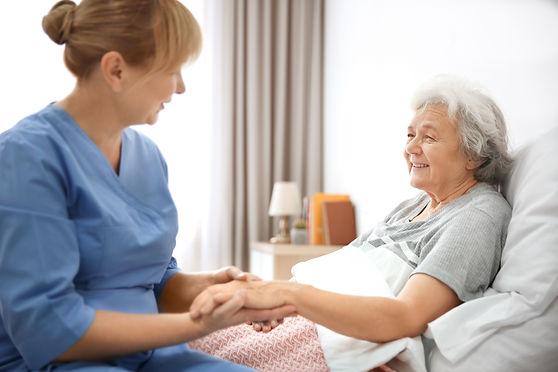 Caregiver massaging hand of senior woman at home.jpg
