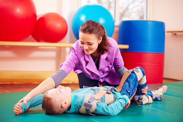 cute kid with disability has musculoskeletal therapy by doing exercises in body fixing bel