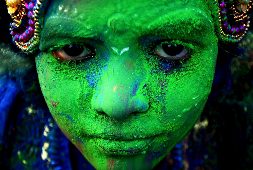 A photo an Indian child covered in green powder.