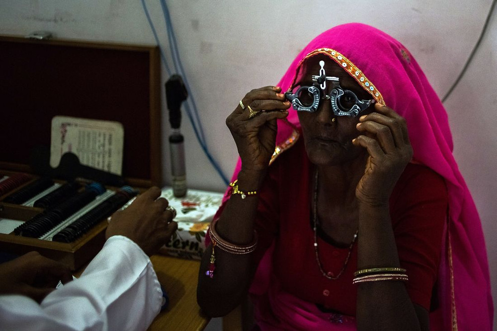 patient adjusts a pair of glasses used to test eyesight during an examination