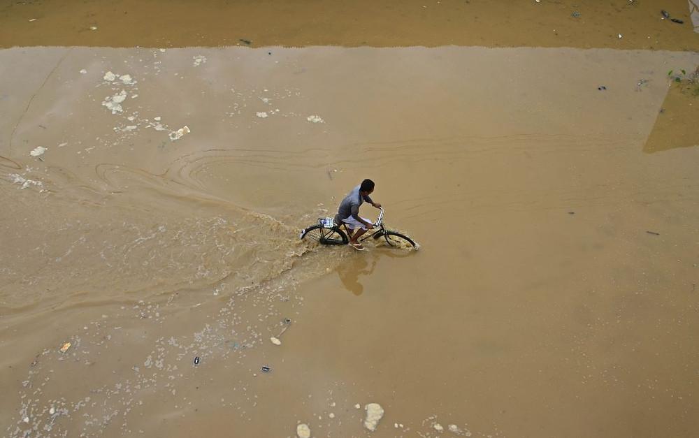 A cyclist pedals through flood water after heavy rain in Dimapur