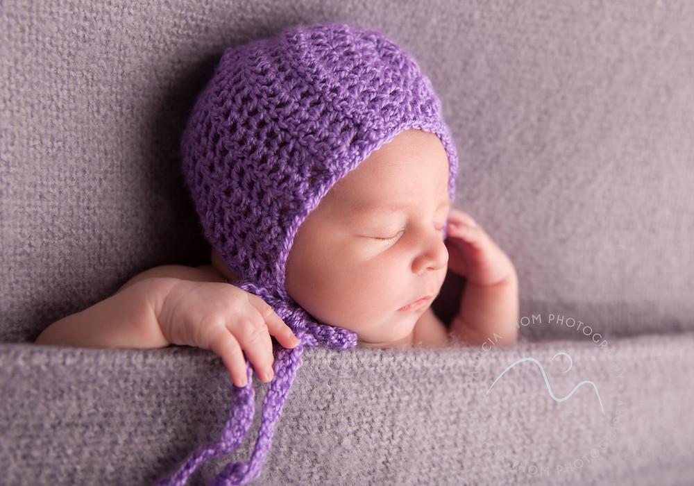 Baby sleeping wearing purple hat