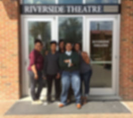 Five women pose, smiling together in front of the Riverside Theatre entrance.