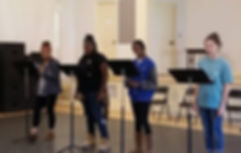 Four women stand behind music stands performing to an unseen audience