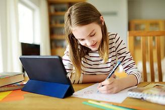 Preteen schoolgirl doing her homework wi
