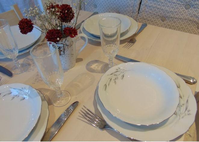 Table-dressee-pour-4-personne-vaisselle--blanche-et-verres-a-pied-un-bouquet-de-fleur-rouge-au-centre-de-la table