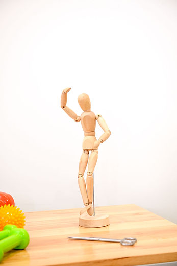A timber model of a dancing figure sitting on a timber bench with some scissors and some brightly-coloured dumbbells and massage balls.