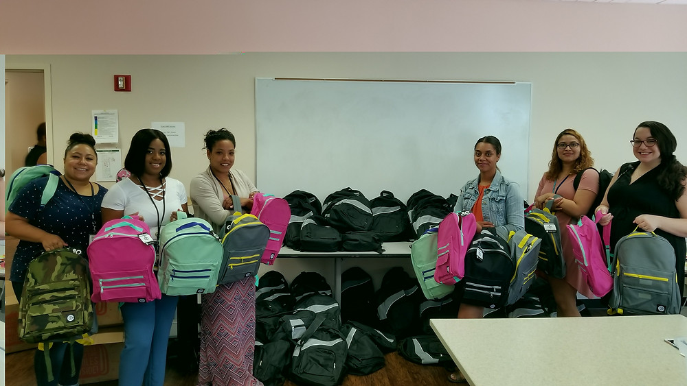 Clifford Beers staff pose with filled backpacks during the stuffing party.