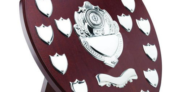 MAHOGANY SHIELD WITH CHROME FRONTS AND 13 RECORD SHIELDS (1in CENTRE) - 14in