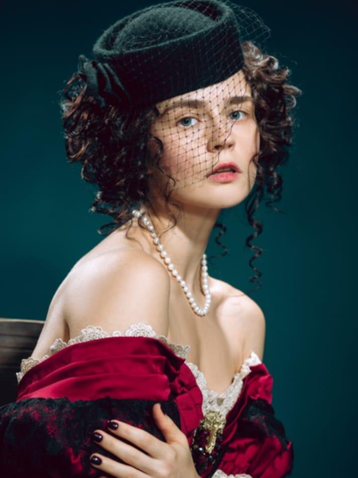 Mulher jovem como Anna Karenina isolada em azul escuro