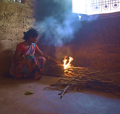 Woman cooking on traditional chulha.png