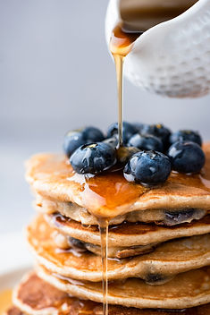 Maple syrup pouring on stack of pancakes