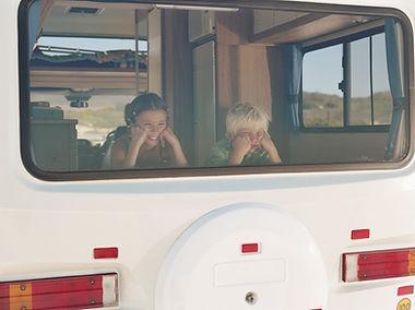 Junge und Mädchen im Campervan Fenster