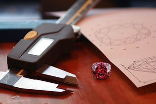 Faceted spinel, beside gem calipers
